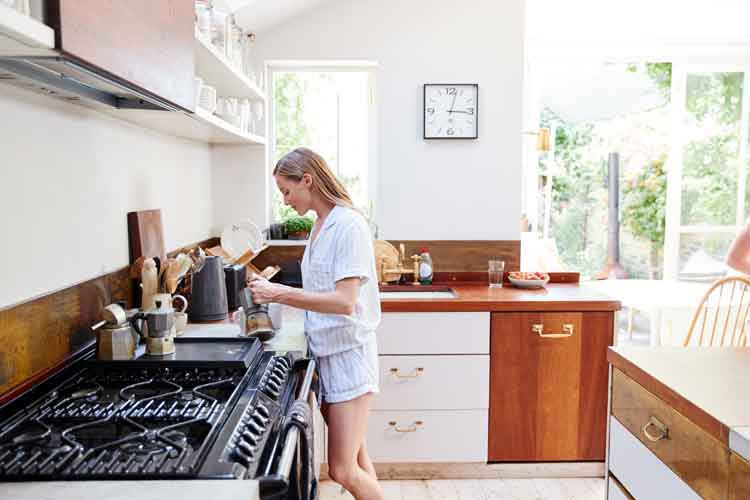 Image of woman making breakfast in beautiful modern kitchen featuring solid surface, granite, and engineered stone countertops by Earnest Watkins Construction professional commercial and residential remodeling in Panama City, Florida